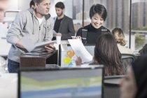 Dos trabalhadores que trabalham no projeto, no ambiente de escritório ocupado — Fotografia de Stock