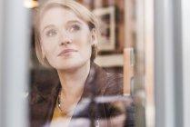 Primo piano di giovane donna che guarda fuori dalla finestra — Foto stock