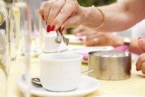 Hand, Zuckerwürfel in die Kaffeetasse — Stockfoto