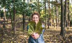 Smiling woman holding autumn leaf in the forest — Stock Photo