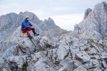 Spain, Picos de Europa, mountaineer resting on rock — Stock Photo