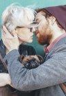 Giovane coppia innamorata baciare con cane tra di loro — Foto stock