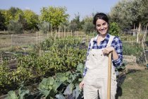Lächelnde Gärtnerin steht auf Bauernhof und blickt in die Kamera — Stockfoto