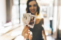 Young woman holding polaroids of herself, showing at camera — Stock Photo