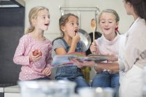 Caucasian cute mother and daughters in kitchen together — Stock Photo