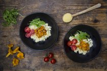Bowls of couscous salad with tomatoes, rocket and chanterelles on wood — Stock Photo