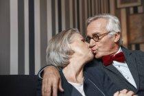 Старший добре одягнений, пару цілуватися на дивані — стокове фото
