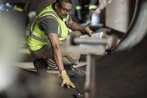 Engineer examining construction parts at workshop — Stock Photo