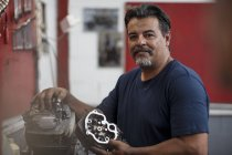 Motorcycle mechanic holding vehicle part in workshop — Stock Photo