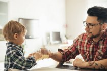 Father and son clinking juice glasses in kitchen — Stock Photo