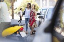 Madre e figlia che camminano insieme con le borse della spesa in strada trafficata della città — Foto stock