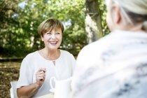 Felice donna anziana socializzare con un amico all'aperto — Foto stock