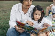 Grandmother showing picture book to granddaughter on meadow — Stock Photo