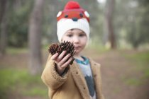 Boy wearing woolly hat in forest holding pine cones — Stock Photo