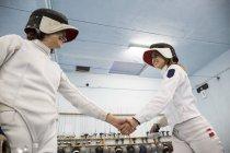 Esgrimistas femininas, apertando as mãos depois de um combate de esgrima — Fotografia de Stock
