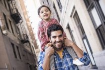Happy father carrying daughter on shoulders walking by street — Stock Photo