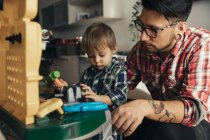Father and son playing together on toy workbench — Stock Photo