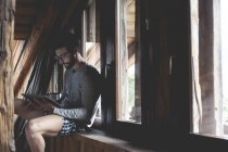 Portrait of young man using tablet on window sill — Stock Photo