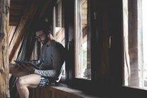 Портрет молодої людини за допомогою планшетного ПК на підвіконня — стокове фото