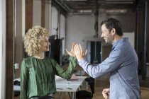 Счастливый человек и женщина давая высокие пять в офисе — стоковое фото