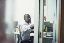 White collar worker sitting in office, sticking notes on glass walll — Stock Photo