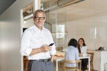 Uomo d'affari fiducioso con cellulare in ufficio con dipendenti in background — Foto stock