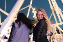 Два щасливі молодих жінок, що стояли на парк атракціонів вночі — стокове фото