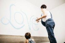 Petit garçon en regardant sa mère peignant le mur — Photo de stock