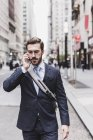 Empresário no celular andando na rua — Fotografia de Stock