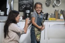 Caucasian cute mother and daughter in kitchen together — Stock Photo