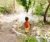 Ragazzino che gioca con tubo da giardino — Foto stock