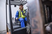 Female on forklift machine wearing safety gear and overalls — Stock Photo