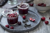 Closeup view of cranberry jam in jars with berries on tray — Stock Photo