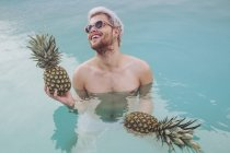 Smiling young man holding pineapples in swimming pool — Stock Photo