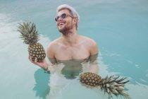 Joven sonriente sosteniendo piñas en la piscina - foto de stock