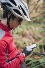 Mountainbiker mit Smartphone bei einer Rast in der Natur — Stockfoto
