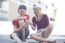 Boy and girl using smartphone while sitting on skateboard — Stock Photo