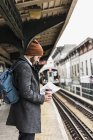 Jovem esperando na plataforma da estação de metro, lendo documentos — Fotografia de Stock