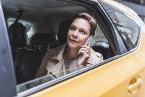 Femme d'affaires à l'aide de téléphone portable dans le taxi — Photo de stock
