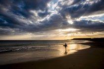 Fernsicht auf Teenager-jungen mit Surfbrett am Strand bei Sonnenuntergang — Stockfoto
