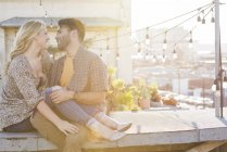 Couple cuddling on sunny rooftop, Los Angeles, USA — Stock Photo