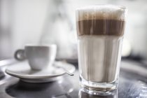 Close-up of Latte Macchiato and cup on tray — Stock Photo