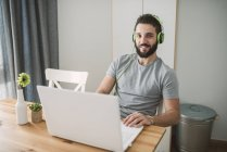 Young smiling man using laptop at home — Stock Photo