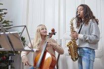 Duas garotas tocando violoncelo e saxofone na árvore de Natal — Fotografia de Stock