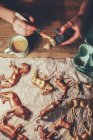 Overhead view of woman painting animal figurines with paint — Stock Photo