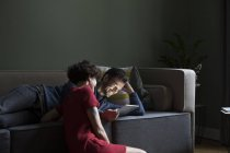 Couple relaxing together in the living room and sharing digital tablet — Stock Photo