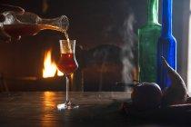 Рука розливу лікер у чарку в передній частині відкритого вогню — стокове фото
