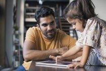 Père regardant enfant en bas âge fille en utilisant tablette numérique assis sur la table de cuisine — Photo de stock