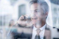 Adulte caucasien homme d'affaires lors d'un appel au bureau — Photo de stock