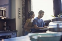 Woman embracing man sitting at table in kitchen — Stock Photo